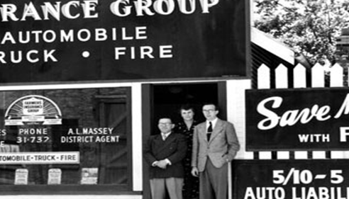 old black and white photo of 3 men in front of a store front.