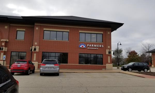 Outside of a brown brick building with a Farmers Insurance sign on the facade