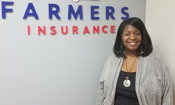 Woman posing in front of Farmers Insurance logo