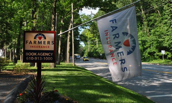 Farmers Insurance - Book Agency sign and Farmers Insurance flag.