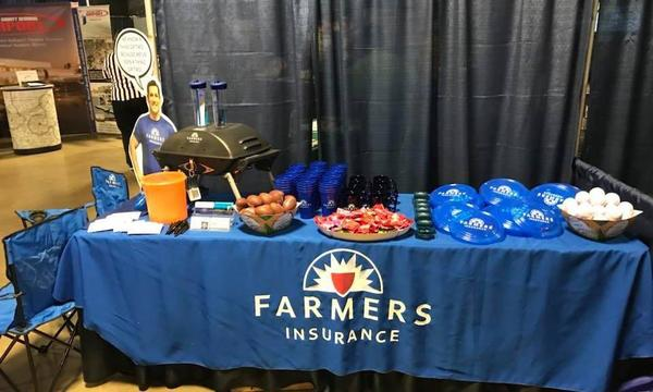 A table draped in a Farmers Insurance tablecloth is covered in snacks and toys