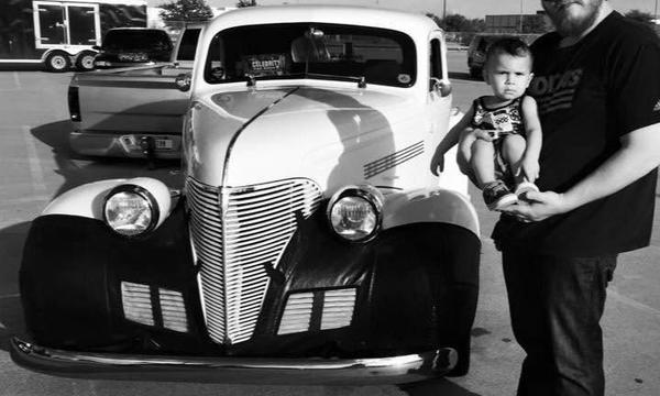 Man holding a baby in front of a classic car