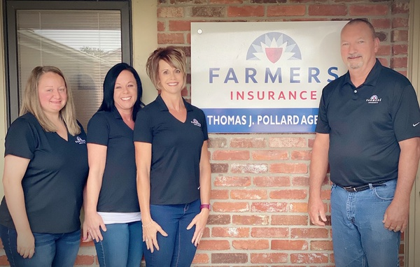 Four people in front of Farmers Insurance store front