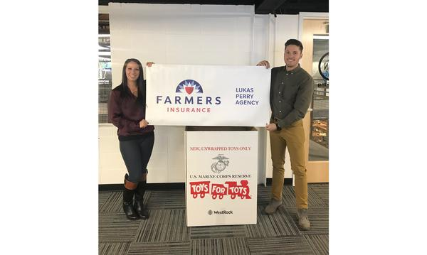 2 staff members holding a Farmers Toys for Tots sign.