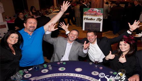 People posing around a casino table