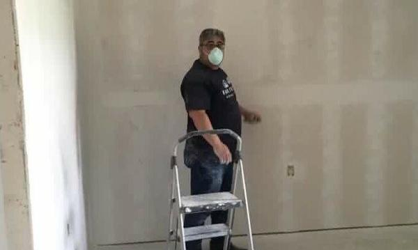 A photo of the Farmers agent sanding walls.