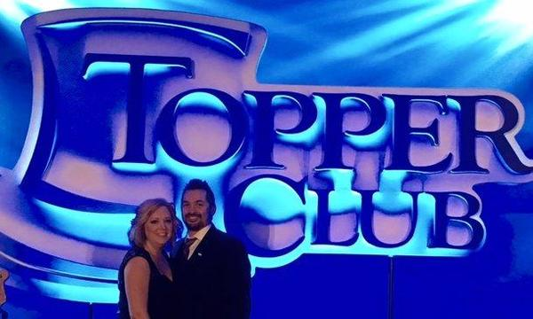 couple in front of toppers club banner