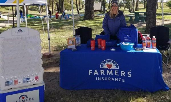 Agent Robin standing at a Farmers Insurance table at a community event.