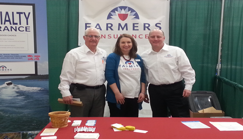 Group photo of two men and a woman at a Farmers booth