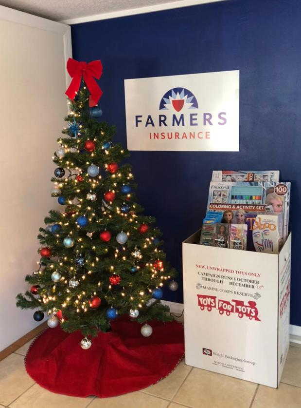 A toys for tots box next to a Christmas tree in the Farmers office