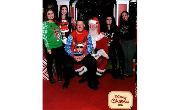 Agent sitting on Santa's lap, with staff members standing alongside