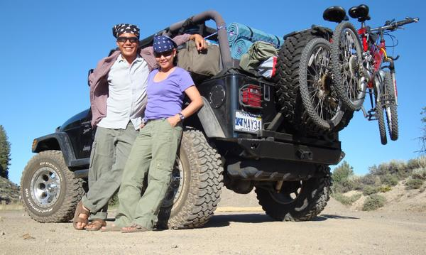 Two people leaning on a Jeep that is parked on a sand dune