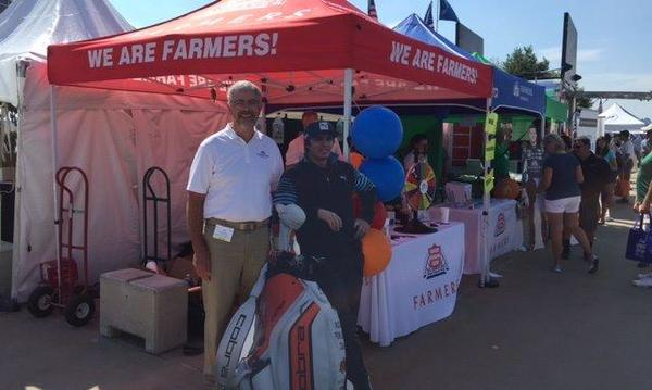 Agent standing with cardboard cutout of golfer in front of a Farmers Insurance tent