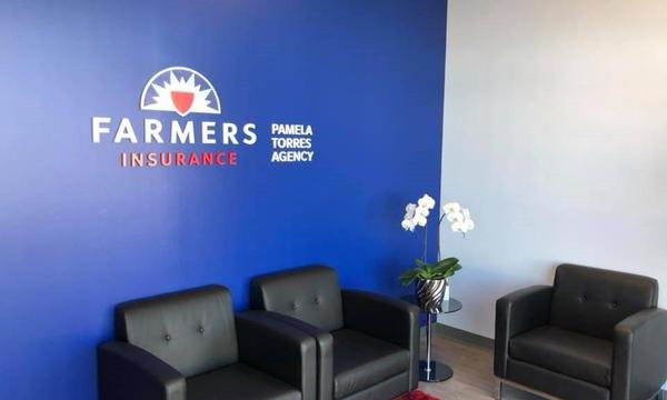 Interior of agency, with large blue wall with farmers logo.