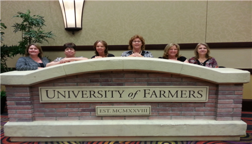 Six women standing behind a stone University of Farmers sign.