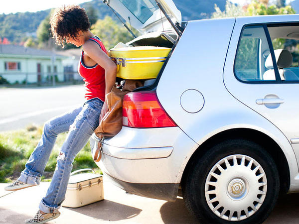 girl packing suitcases into a car