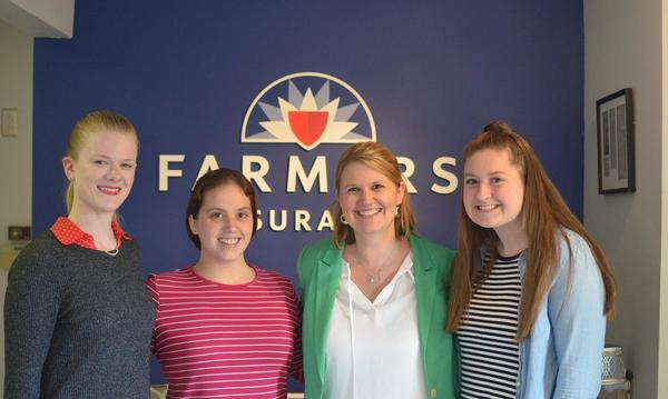 Farmers agency staff posing in front of Farmers logo