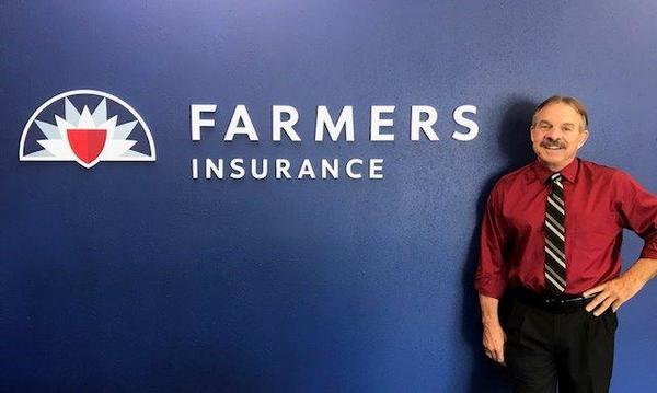 Man in front of Farmers logo on wall