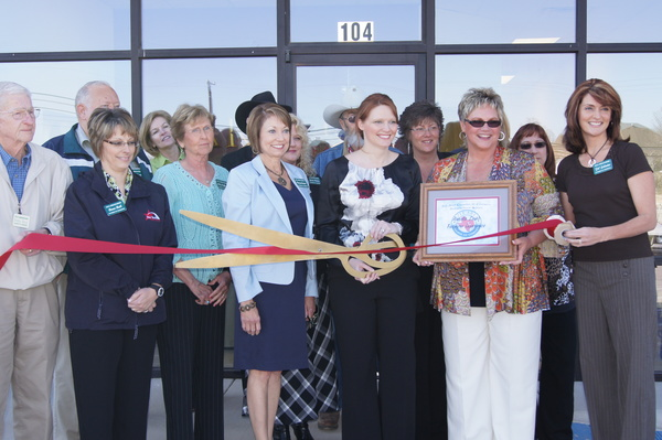 Ladies pose to cut ribbon at Farmers agency