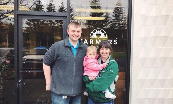A family pose in front of a Farmers storefront