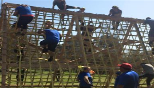The Parmley Agency 5k team climbing obstacles for charity.