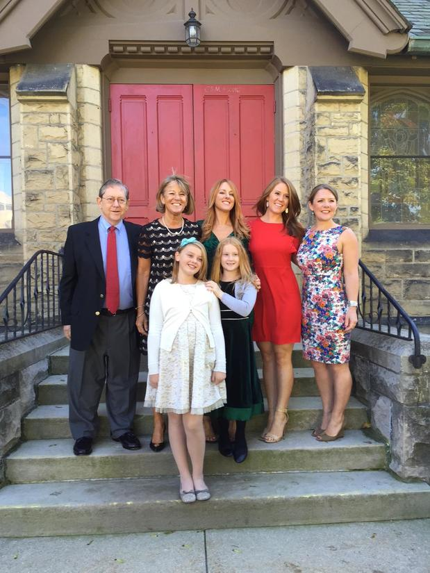 Agent Tom Bernock with his family on stairs of a brick building in front of a red door.
