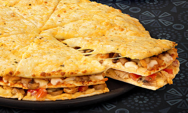 Creamy Chicken Triple-Decker® pizza with 3 layers, abundant toppings, and cheese on a dark wood table.