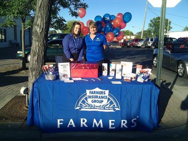 Agent and woman standing behind a Farmers table