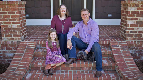family of three sitting on brick steps