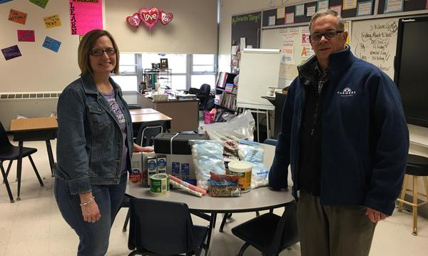 Agent and teacher standing next to a table of school supply donations.