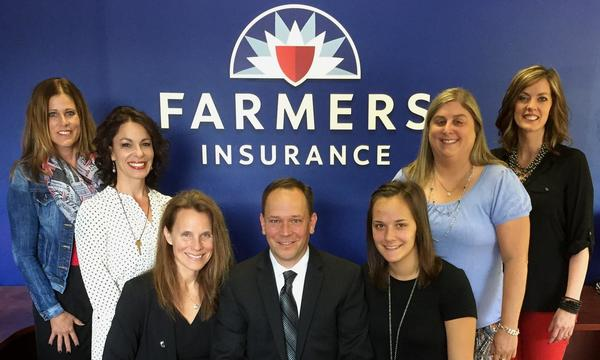 Staff posing in front of the Farmers logo