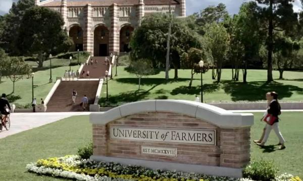 Stone sign displaying University of Farmers on a campus with stairs to the school in the back.