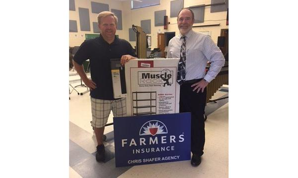 Agent Chris Shafer standing with a male teacher next to the Farmers Insurance logo and a box of shelves.