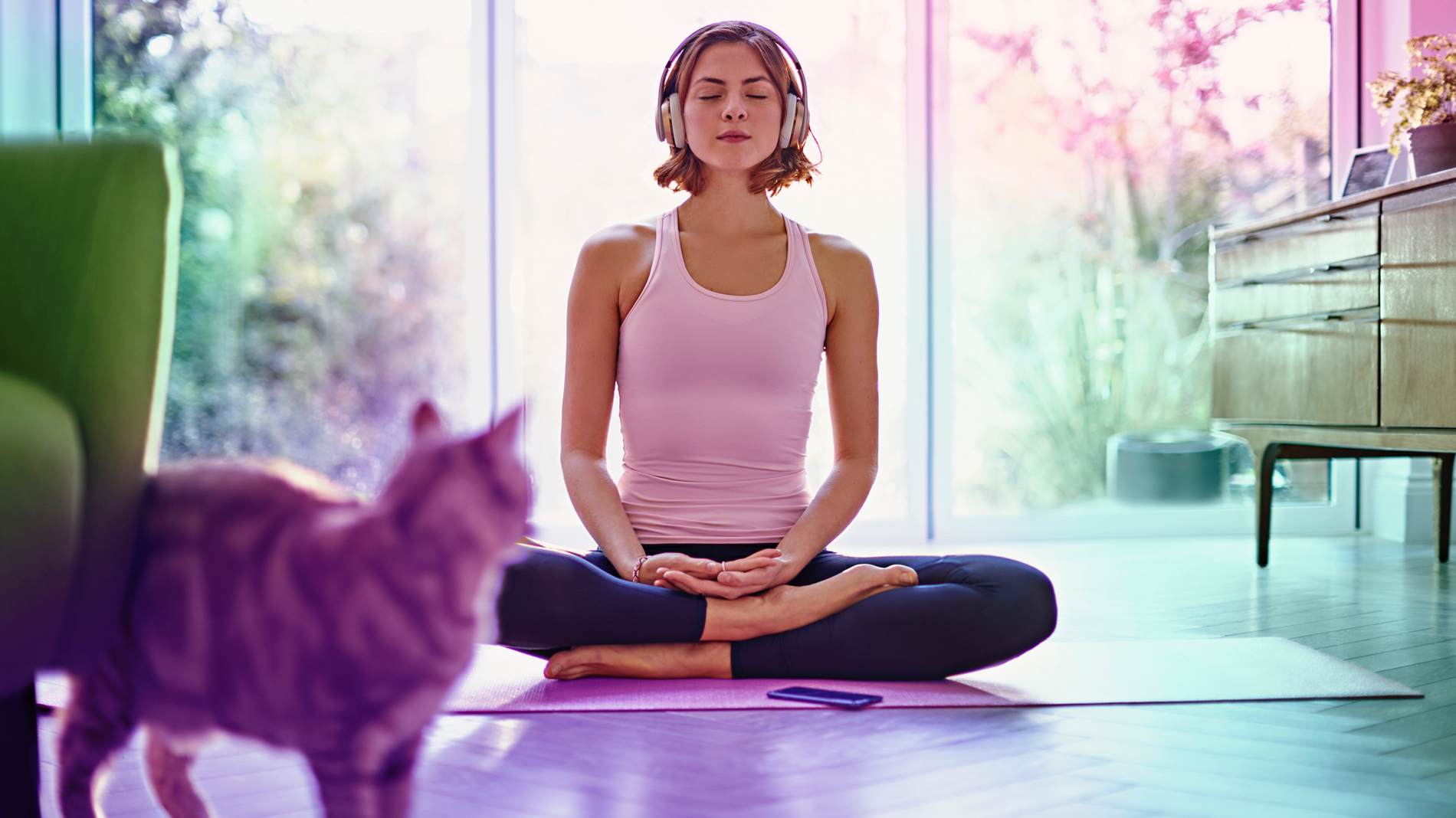 A woman sits on a yoga mat in a living room while wearing large headphones streaming meditation music through her Three Mobile Network on her cell phone that rests on the floor in front of her.