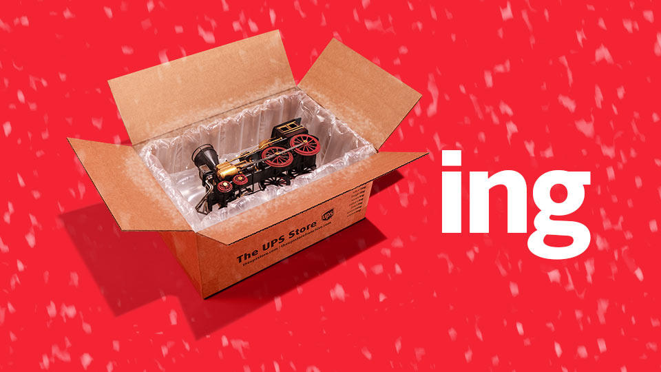 Toy train in a The UPS Store box on a red background with snow next to the letters ING