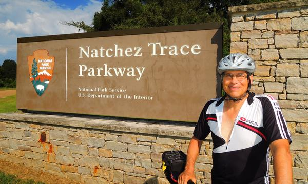 Agent with his bicycle in front of sign of Parkway