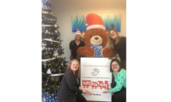 The Jodie Satterfield Agency posing with the office's official drop-off box for Toys for Tots.