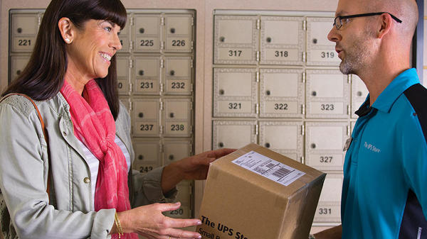 associate handing mailbox customer woman her package