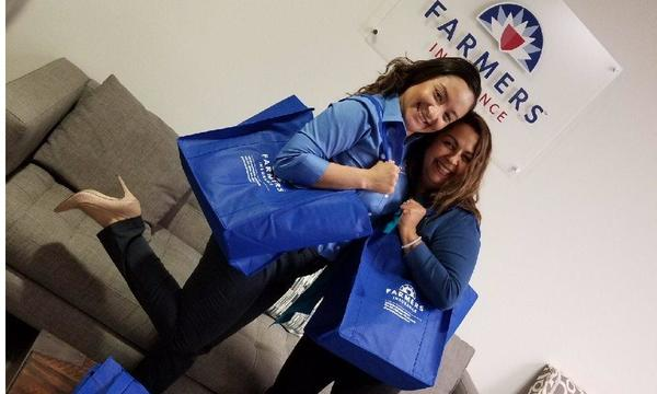 Two girls smiling with blue Farmers tote bags.