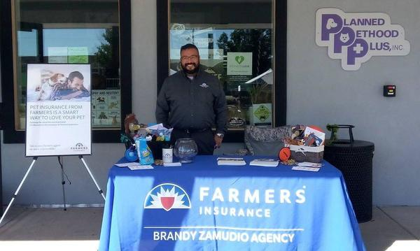 Agent Brandy Zamudio in front of a booth at a pet fair