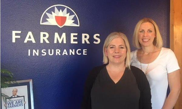 Agent and staff in front of Farmers logo