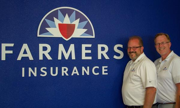 Agent Victor Thompson and another man standing next to the Farmers logo on a wall.