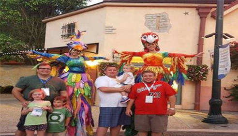 A family standing in front of people in colorful bird costumes.