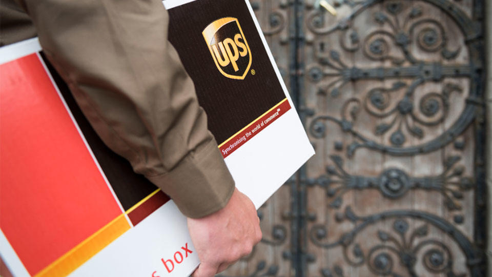 Close up of UPS delivery driver standing in front of door