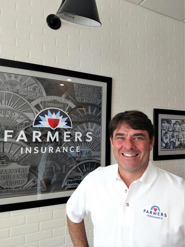 man smiling in front of farmers insurance picture