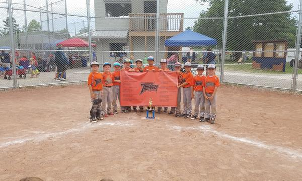 A little league baseball team posing with their banner and a trophy, on the home plate of the baseball diamond.