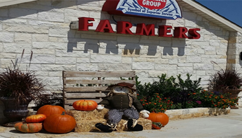 Decorations of hay, pumpkins and a scarecrow outside a Farmers office.