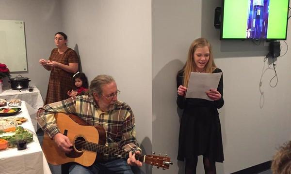 Man with guitar sits next to a girl who is singing and holding a piece of paper
