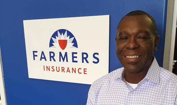 Michael Benham Agency staff member, Wilbert Collins, in a collared shirt next to the Farmers logo on a blue wall.