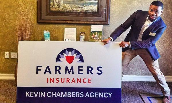 Agent Kevin pretending to pull a Farmers Insurance sign.